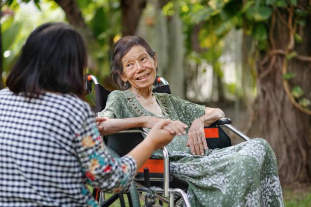Ältere Frau im Rollstuhl zu Hause mit Tochter kümmern sich – Foto