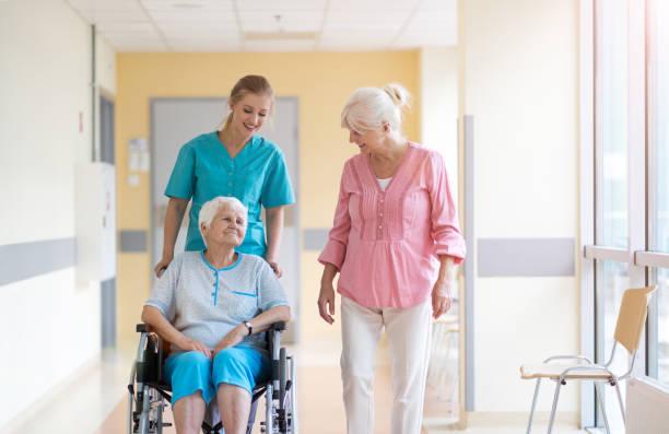 Ältere Frau im Rollstuhl mit ihrer Tochter und Krankenschwester – Foto