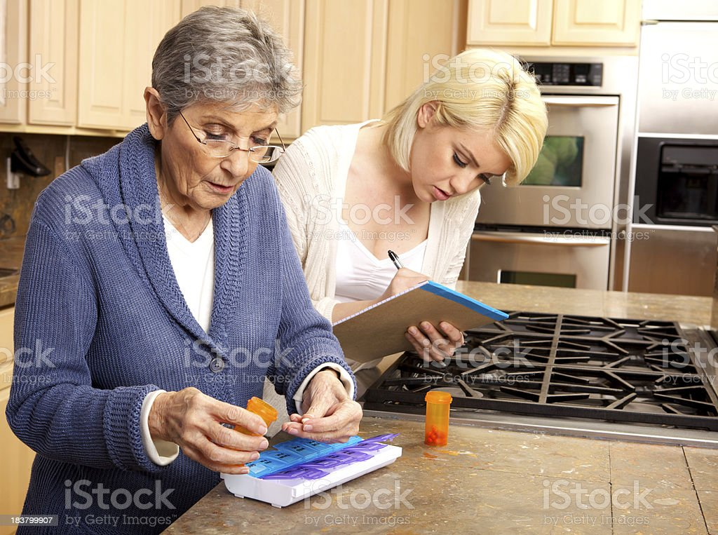 Elderly Woman Organizing Medicine in Pill Box with  Caregiver's Help stock photo