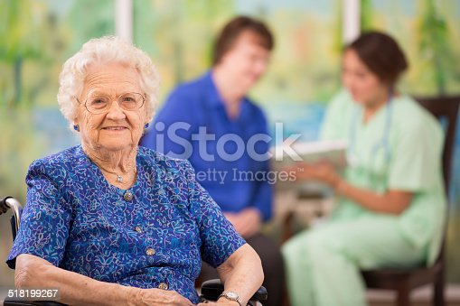 Over 100 year old woman in foreground as her daughter and home healthcare nurse talk about her treatment options in background. Nursing home, doctor's office, or home setting.