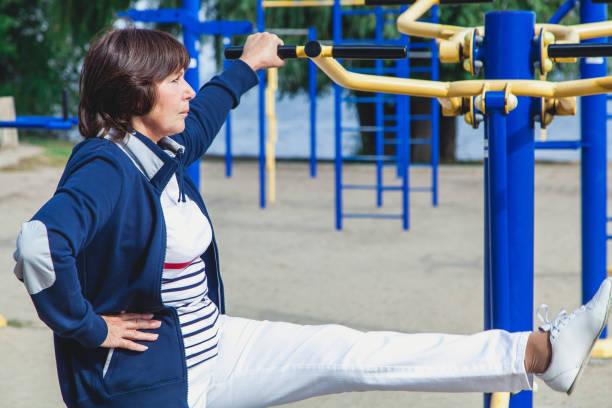 ältere frau führt übungen auf den simulatoren auf sommer sportplatz - granny legs stock-fotos und bilder