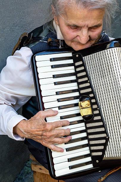 Elderly woman playing accordion. stock photo