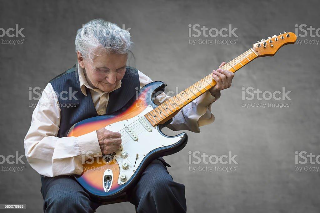 Elderly woman playing guitar. stock photo