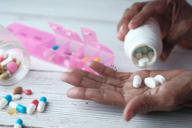 ältere frau gießt pillen aus der flasche auf der hand, top-ansicht - medikament stock-fotos und bilder