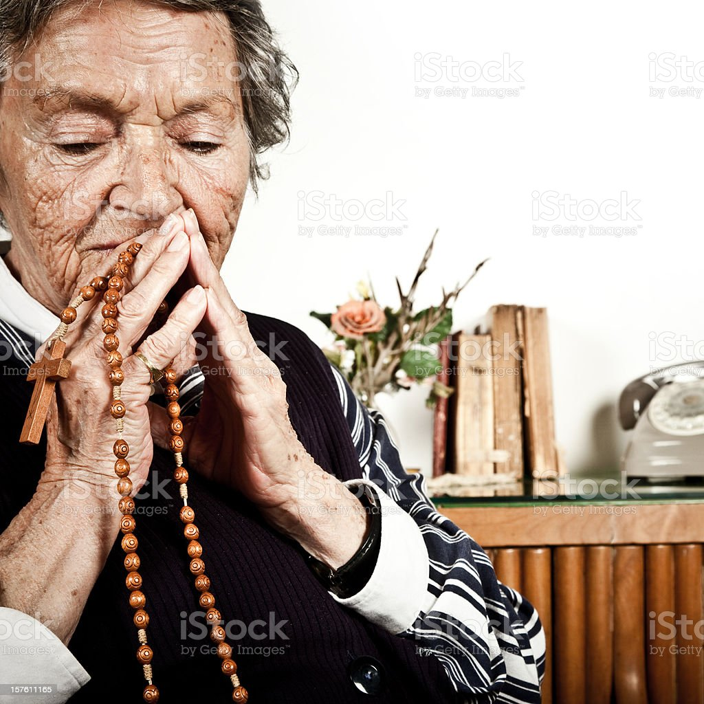 Elderly Woman Praying With Rosary royalty-free stock photo
