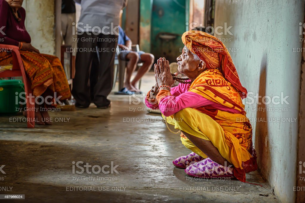 Elderly woman prays in a local retirement home, Nepal stock photo