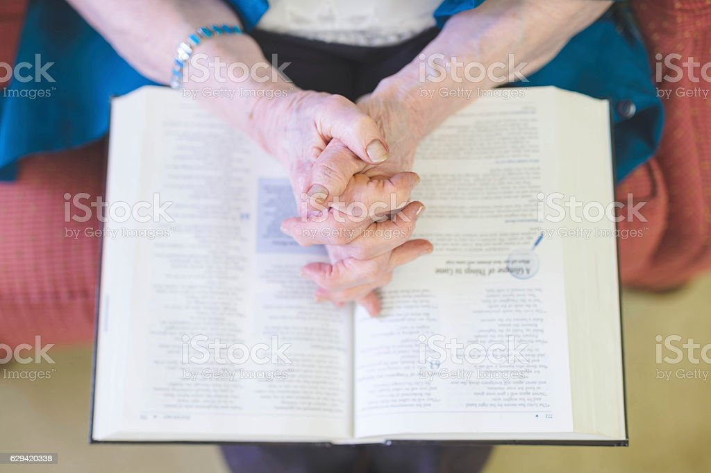 Elderly woman reading the Bible and praying stock photo