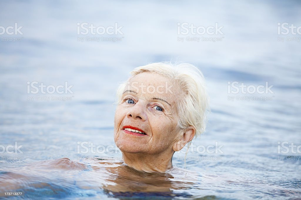 Elderly woman relaxing in water royalty-free stock photo