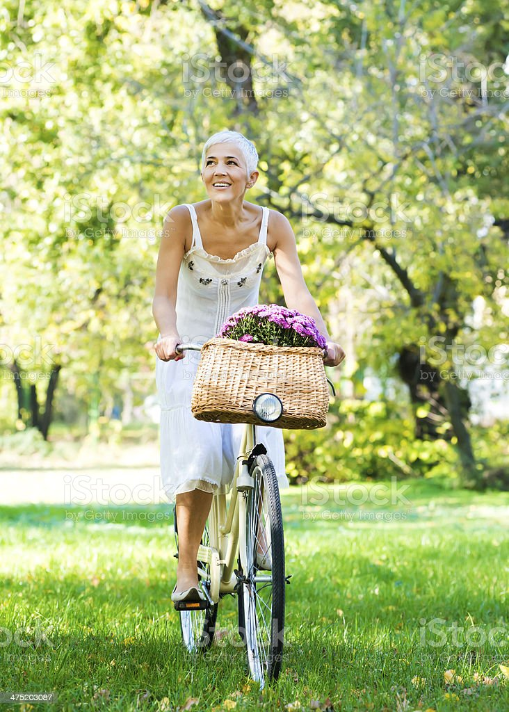 Elderly woman riding a bicycle in a park stock photo