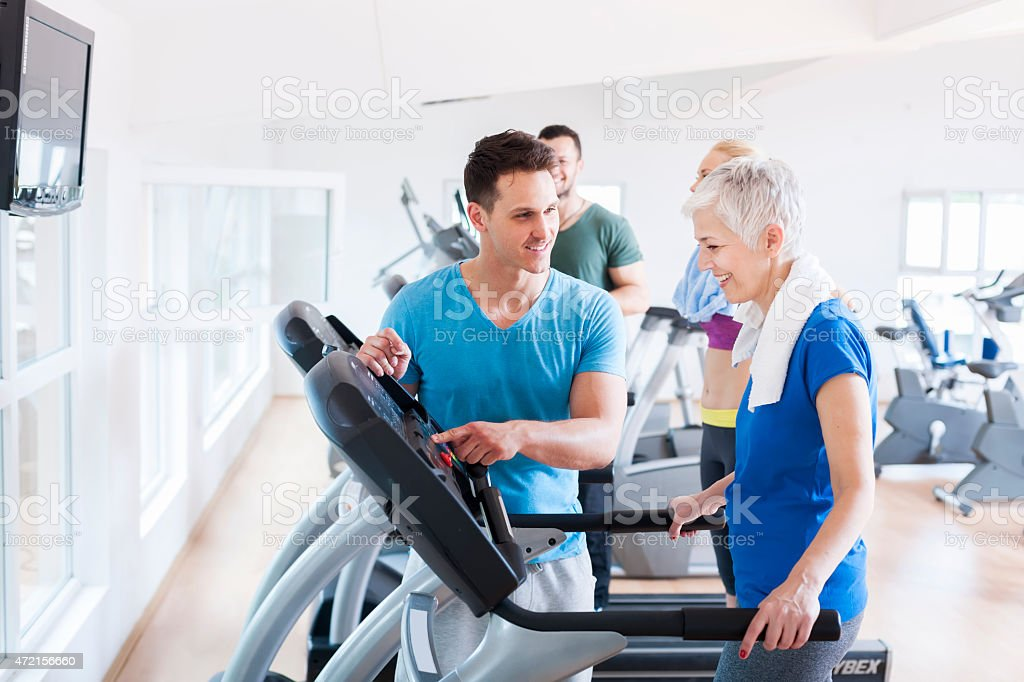 Elderly woman running on a treadmill at the gym stock photo