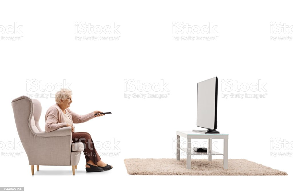 Elderly woman seated in an armchair watching television stock photo