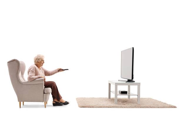 ältere frau sitzt in einem sessel vor dem fernseher - alte serien stock-fotos und bilder