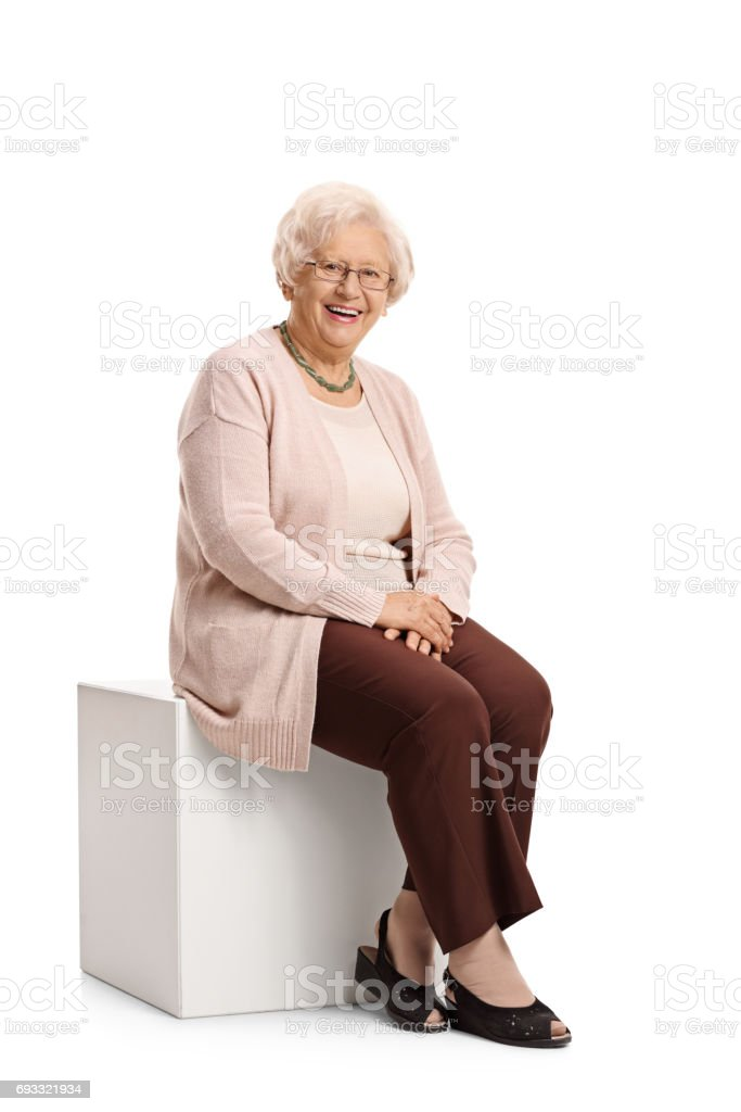 Elderly woman seated on a cube royalty-free stock photo