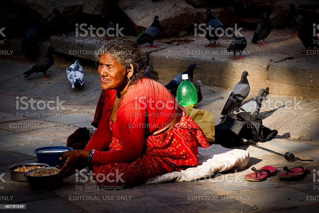 Elderly woman selling bird food at Durbar Square, Kathmandu, Nepal stock photo