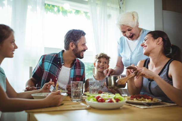 ältere frau servieren mahlzeit zu ihrer familie - seniorenwohnungen stock-fotos und bilder