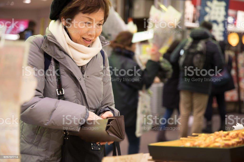 Elderly woman shopping at market stock photo