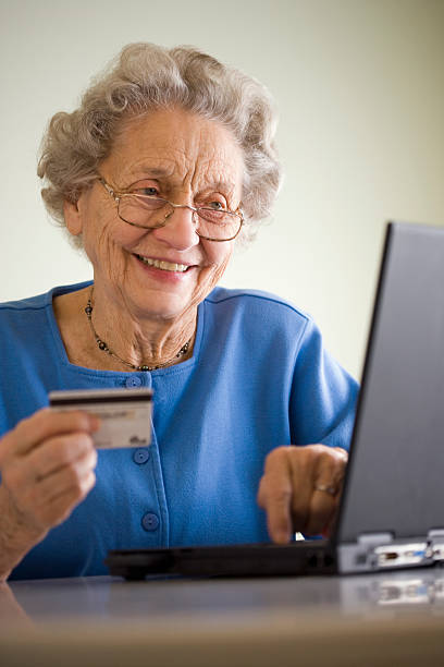 Elderly woman shopping online stock photo