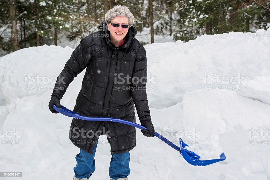 Elderly Woman Shoveling Snow stock photo