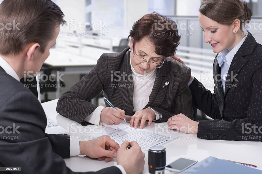 elderly woman signing a document stock photo