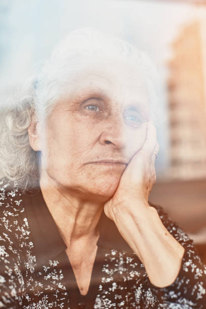 Elderly woman sitting alone and looking sadly outside the window stock photo