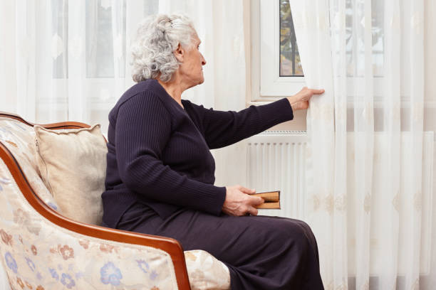 Elderly woman sitting alone with a book in hand and looks sadly outside the window stock photo
