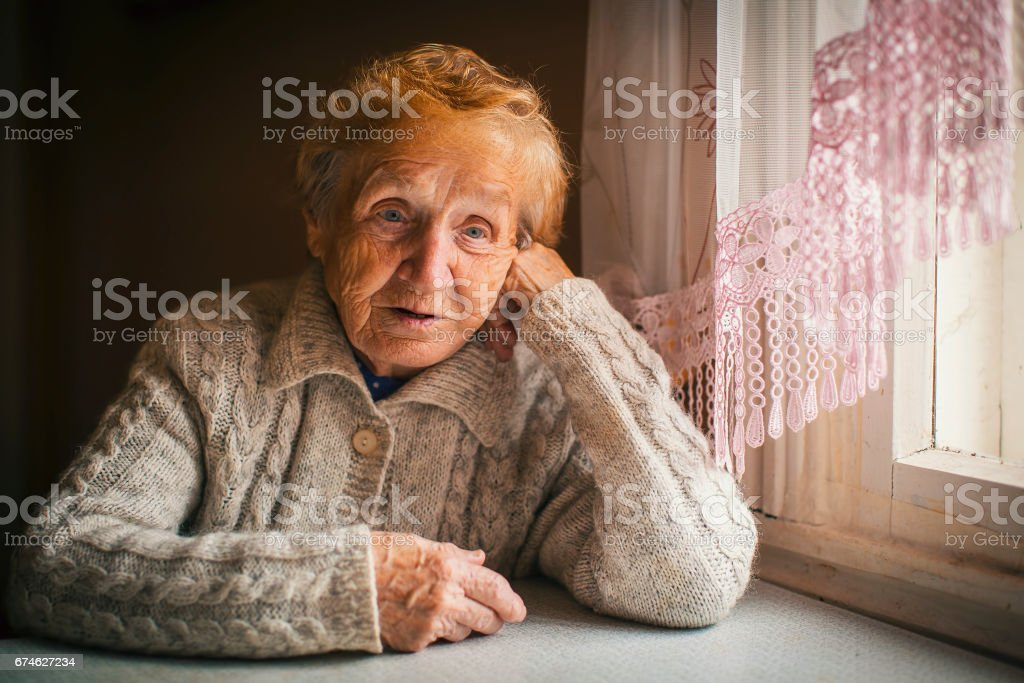 Elderly woman sitting at a loss. An old age pensioner. stock photo