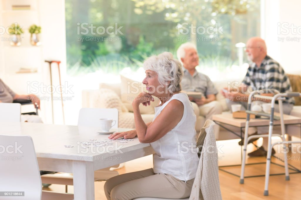 Elderly woman sitting at table stock photo