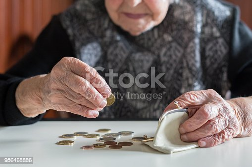 istock Elderly woman sitting at the table counting money in her wallet. 956468886