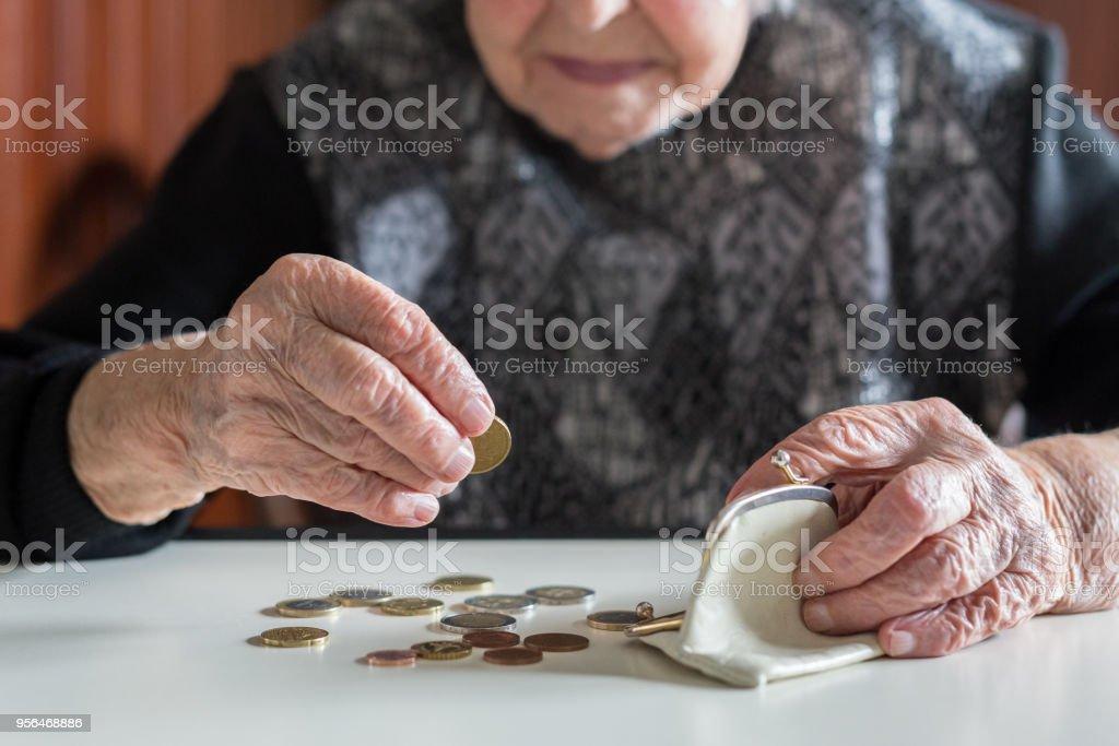 Ältere Frau am Tisch Geldzählen in ihrer Brieftasche. – Foto