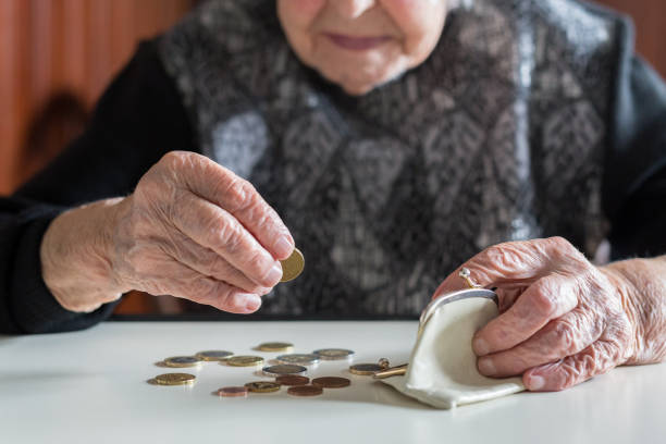 Elderly woman sitting at the table counting money in her wallet. stock photo