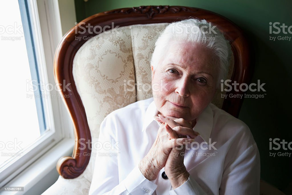 Elderly woman sitting by window stock photo