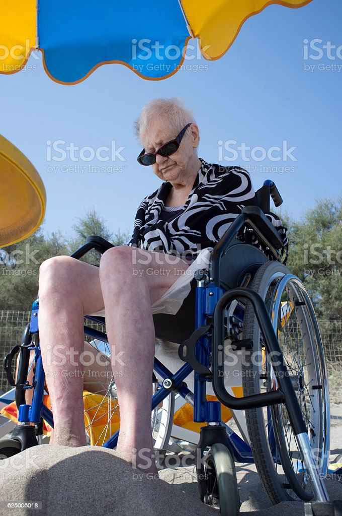 elderly woman sitting in a wheelchair on the beach stock photo