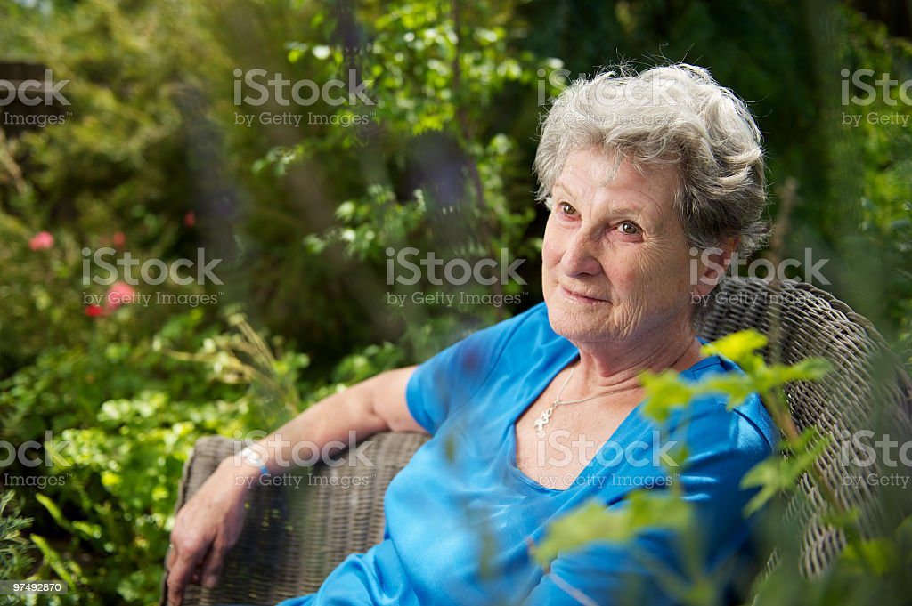 Elderly woman sitting in her garden royalty-free stock photo