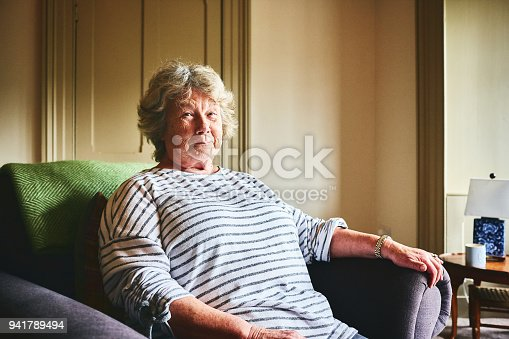 Portrait of elderly woman sitting on armchair in living room at home