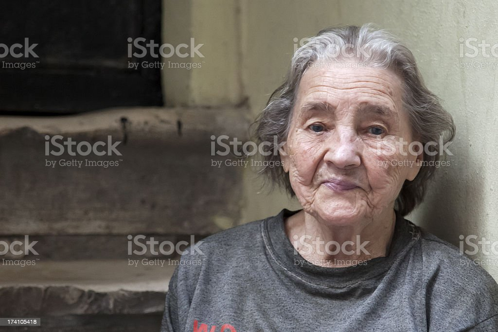 Elderly woman sitting on steps in a run down area stock photo