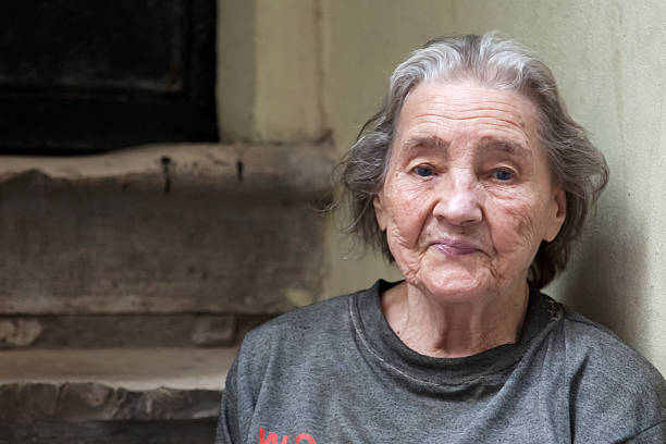 elderly woman sitting on steps in a run down area - homelessness stock photos and pictures