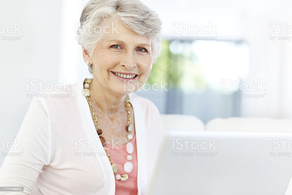 Elderly woman smiles at camera with laptop in front of her stock photo
