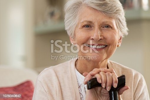 Retired woman with her wooden walking stick at home. Happy senior woman relaxing at home holding cane and looking at camera. Smiling grandmother sitting on couch.