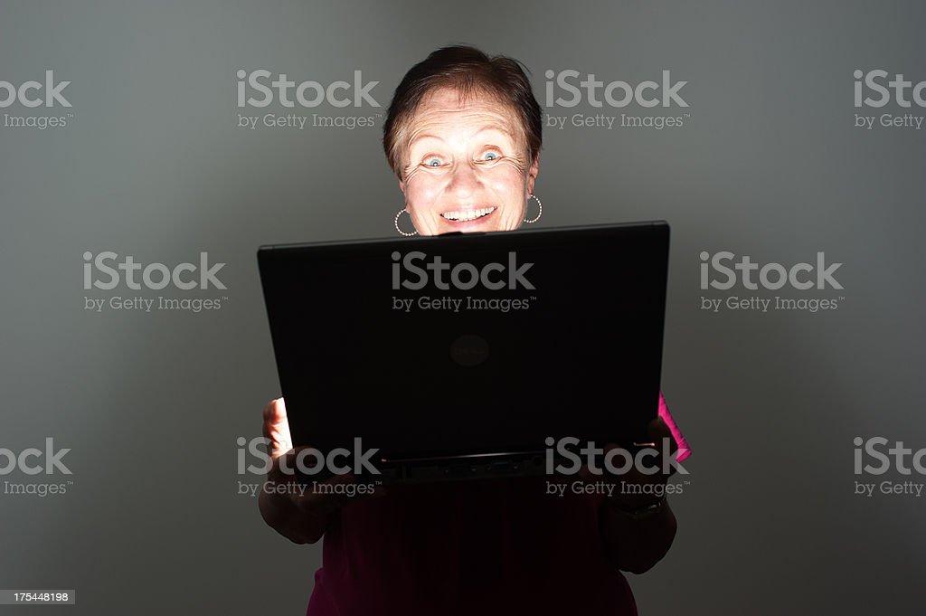 Elderly woman smiling at laptop stock photo