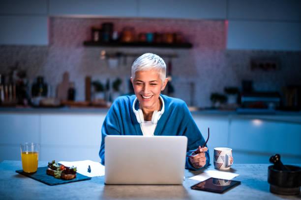 Ältere Frau lächelnd, während der Arbeit zu Hause spät in der Nacht – Foto