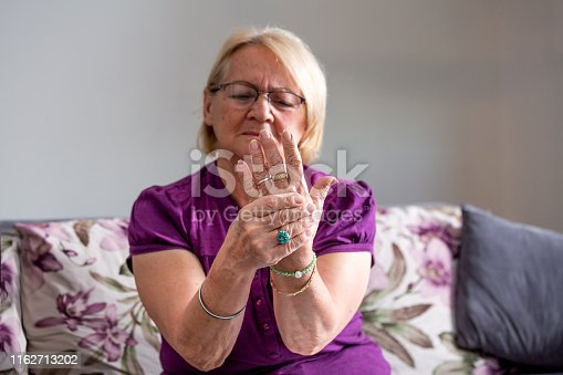 698466046istockphoto Elderly woman suffering from pain in hand, arthritis old person and senior woman female suffering from pain at home 1162713202