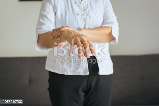 istock Elderly woman suffering with parkinson's disease symptoms 1067210700