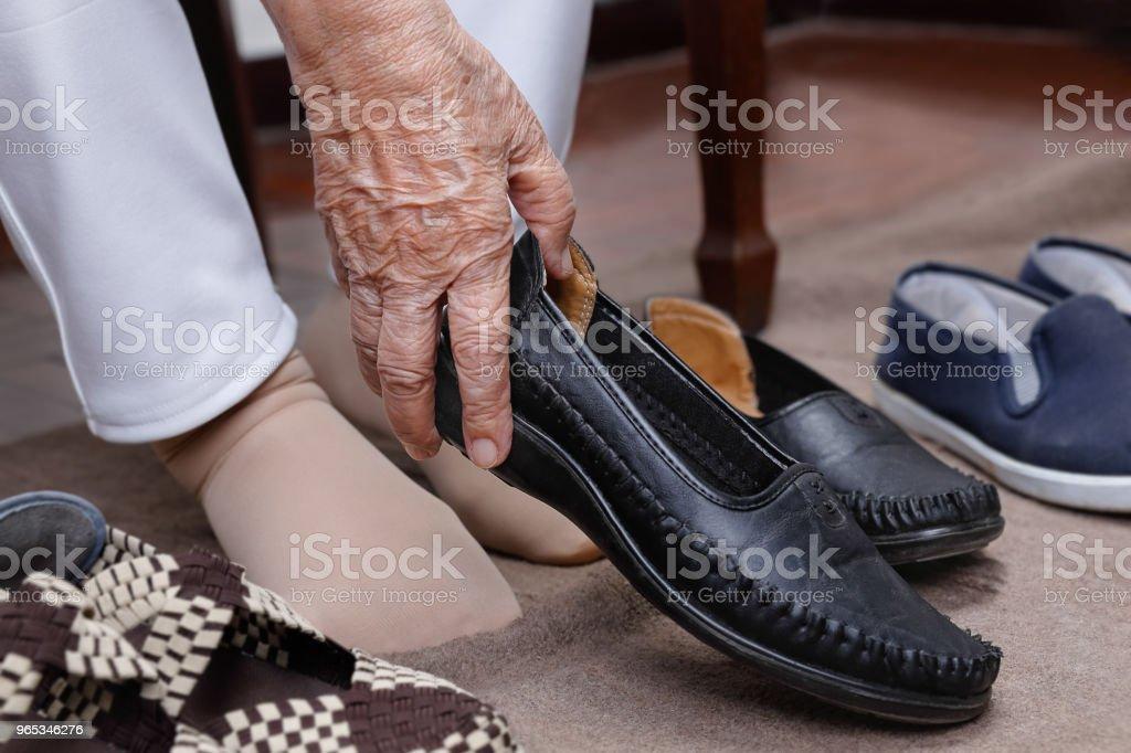 Elderly woman swollen feet putting on shoes zbiór zdjęć royalty-free