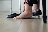 Elderly woman swollen feet putting on shoes