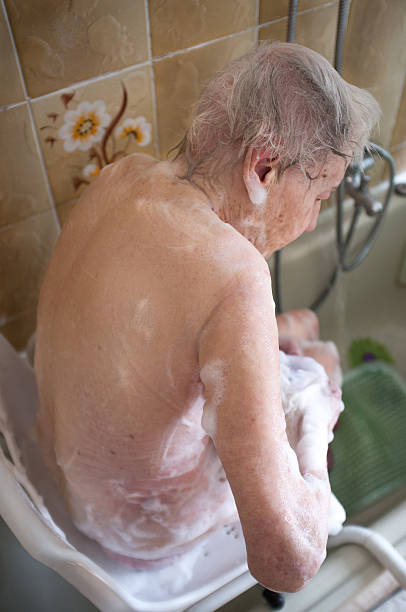 elderly woman taking a shower stock photo