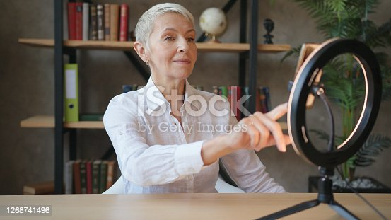 Elderly woman teacher in white shirt talking on videocall on smartphone with LED ring light