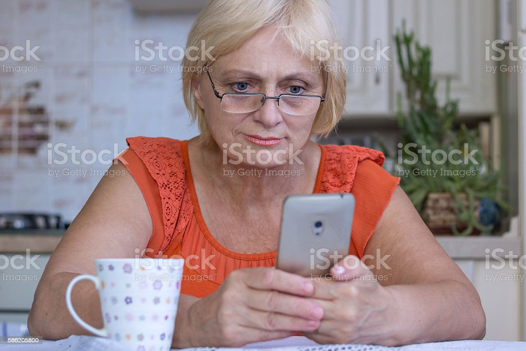Elderly woman texts on mobile phone stock photo