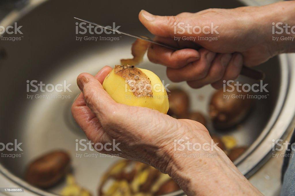 Elderly woman to peel potatoes. Kitchen working. Prepare food royalty-free stock photo