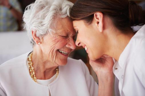 高齢者の女性顔に触れている若い女性の看護師 - 30代のストックフォトや画像を多数ご用意