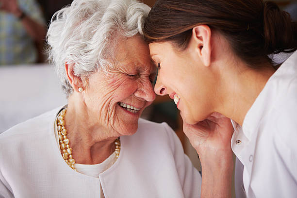 elderly woman touching face of young female nurse - ouderenzorg stockfoto's en -beelden